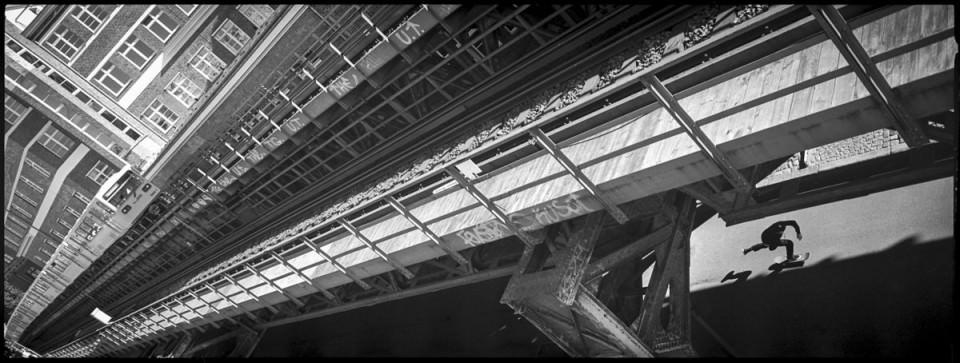 Skater fährt unter einer Bahn-Brücke hindurch.