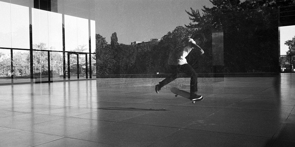 Skater mit Spiegelung einer Fensterfront.