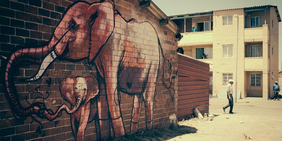 Ein Mann überquert eine Straße, neben ihm ein Wandbild mit Elefanten auf einer Backsteinmauer.