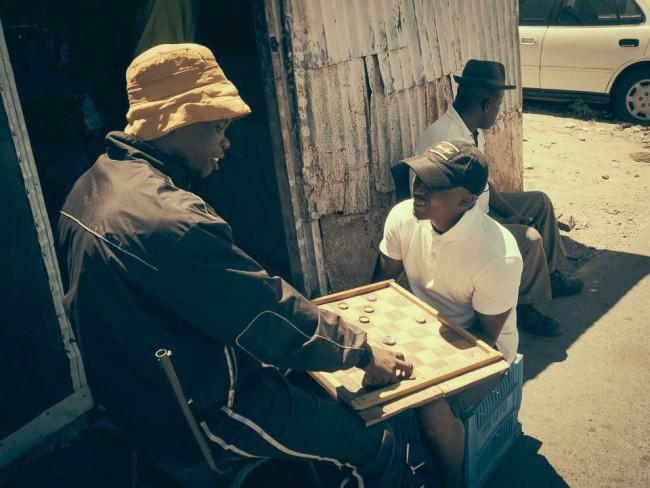 Männer spielen mit Kronkorken Mühle.