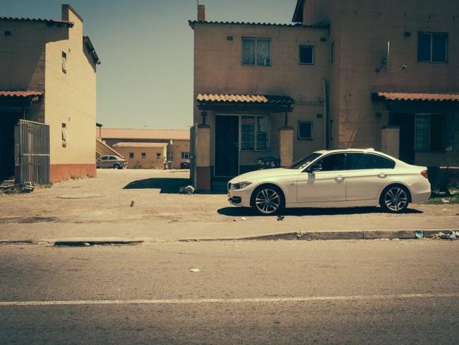 Weißer BMW Coupé in einer heruntergekommenen Umgebung.