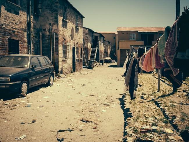 Hinterhof zwischen mehreren Häusern, in dem Wäsche aufgehängt ist und ein Auto steht.