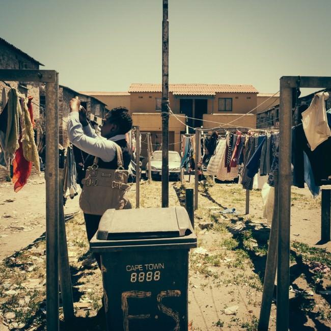 Eine Frai hängt im Freien Wäsche auf eine Leine auf.