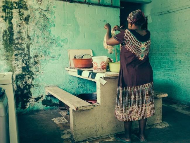 Eine Frau sortiert gewaschene Wäsche in einem türkis gestrichenen Zimmer.