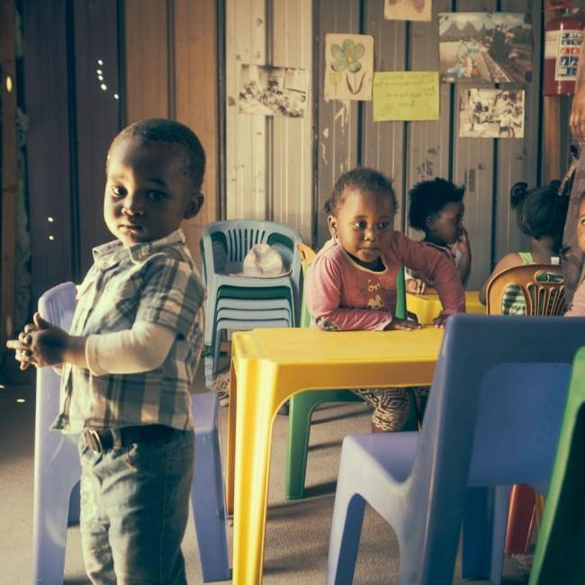 Kinder in einem Kindergarten zwischen bunten Plastikstühlen.