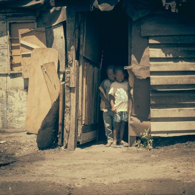 Zwei Kinder stehen in der Tür einer Wellblechhütte und schauen schüchtern heraus.
