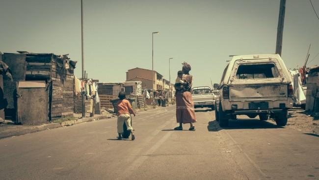 Auf einer leeren Straße gehen eine Frau und ein Kind.