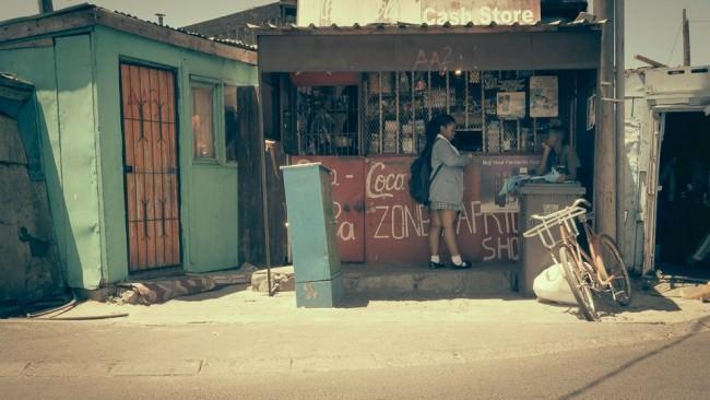 Vor einem Kiosk steht ein Mädchen.