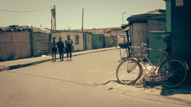 Auf einer leeren Straße zwischen Wellblechhütten laufen drei Jugendliche.