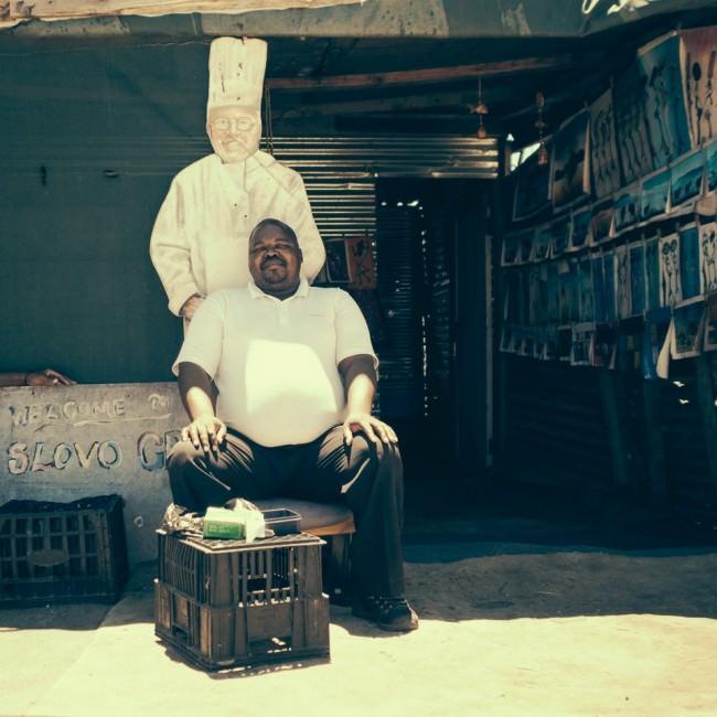 Mann in weiß vor einem Laden sitzend, hinter ihm das Bild eines anderen Mannes ganz in weiß.