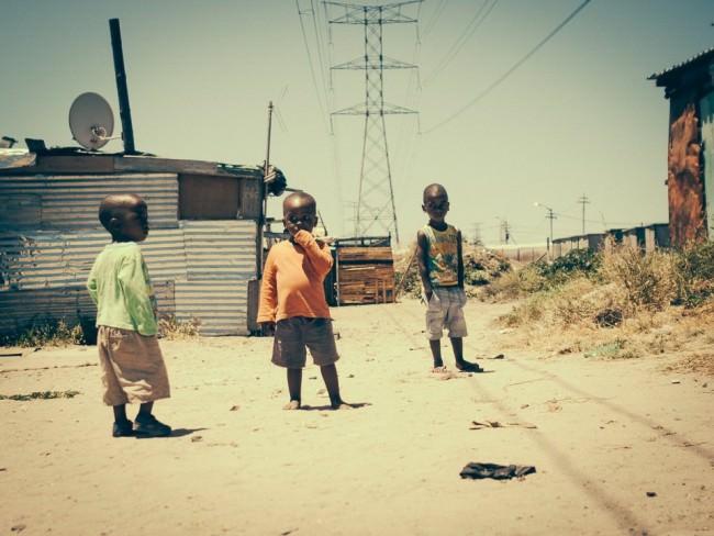 Drei Jungs stehen im Sand vor einer Wellblechhütte.