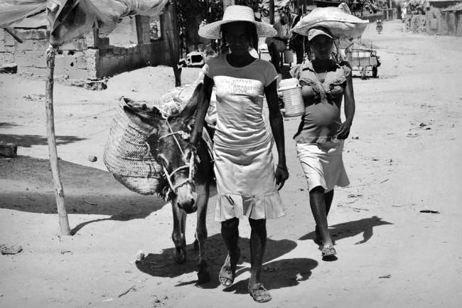 Zwei Frauen sind bepackt mit einem Esel auf einer Sandstraße unterwegs.