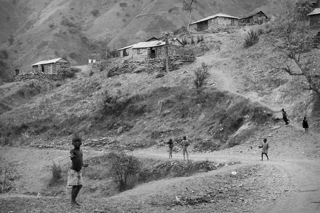Mehrere Kinder vor einer kargen Bergkulisse, in der einige Hütten verstreut sind.