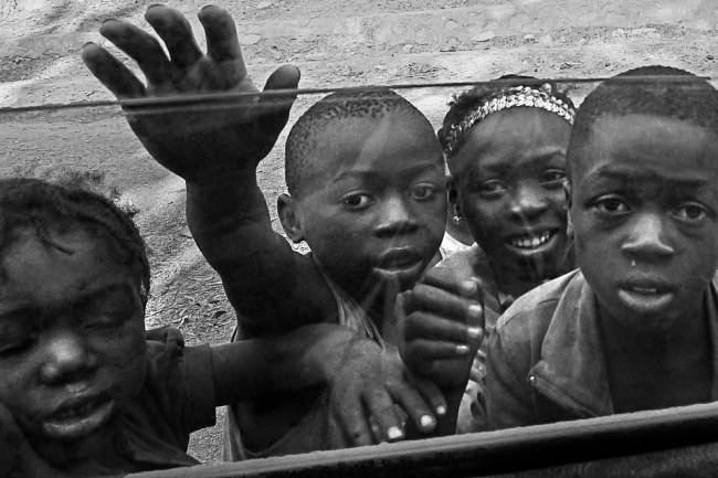 Kinder vor einer Autoscheibe.