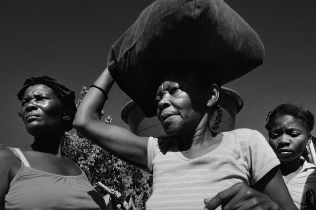 Eine Gruppe Frauen, eine trägt einen Sack auf dem Kopf.