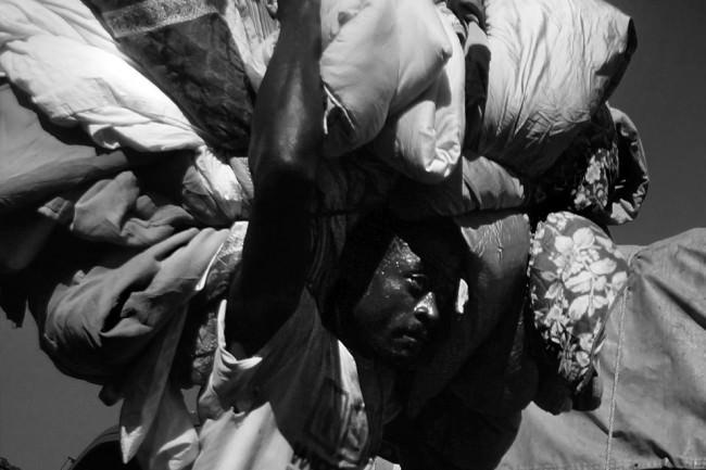 Ein schwitzender Mann, der mehrere Säcke auf dem Kopf trägt.