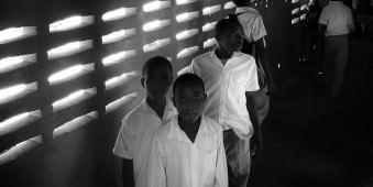 Mehrere Jungen in Schuluniformen vor einer Wand, durch die Licht durch Löcher fällt.