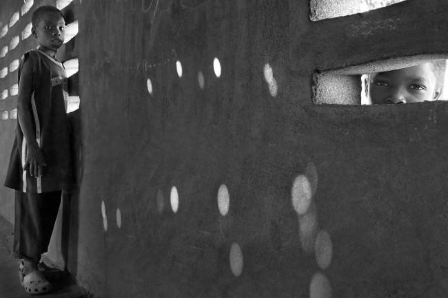 Eine Wand mit Löchern, vor der ein Junge steht und ein anderer durch eines der Löcher schaut.