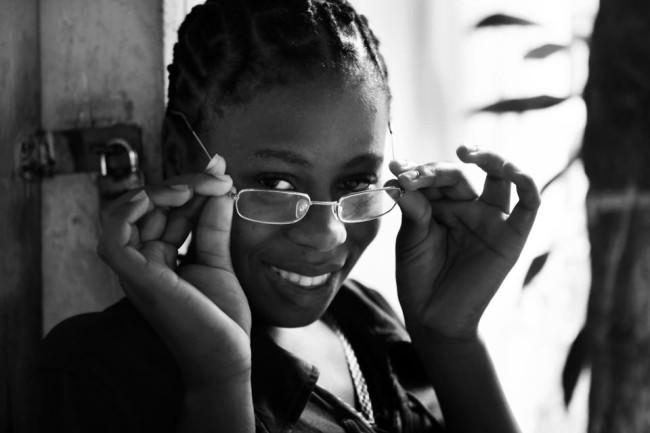 Eine Frau, die sich eine Brille aufsetzt, lächelt.