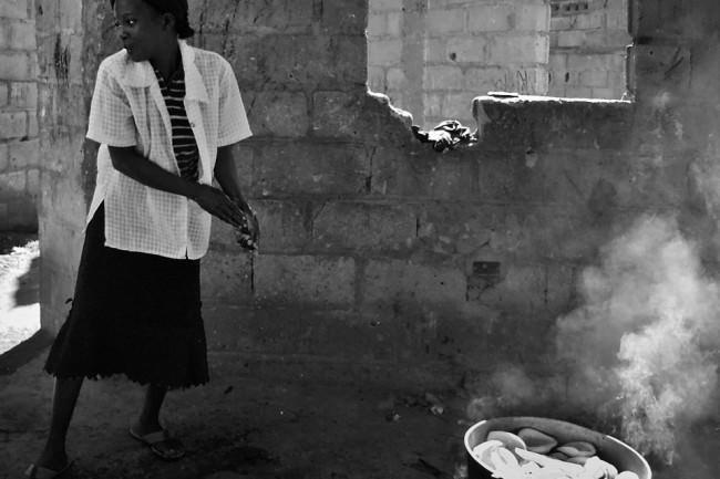 Eine Frau und eine Schüssel vor einer Hauswand.