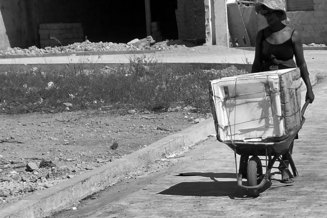 Eine Frau transportiert eine Waschmaschine auf einer Schubkarre.