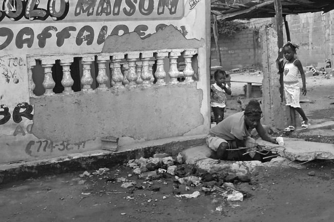 Eine Frau arbeitet in einem Loch vor einem halb zerstörten Haus.