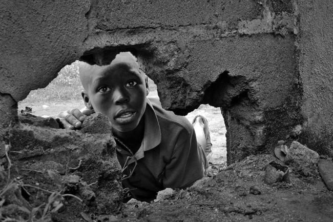 Ein Junge schaut durch ein Loch in einer Mauer.