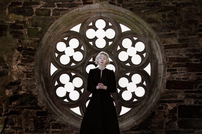 Eine Frau vor einem runden Fenster mit Ornamenten.