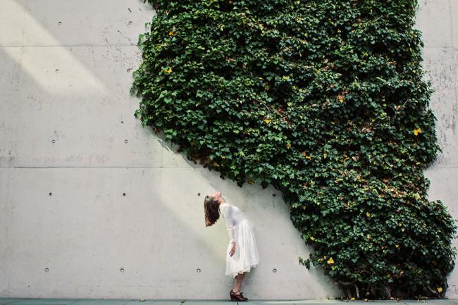 Eine Frau an einer Mauer mit Efeu