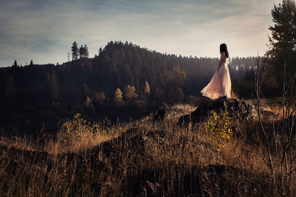 Eine Frau auf einem Stein mit Blick in ein Tal