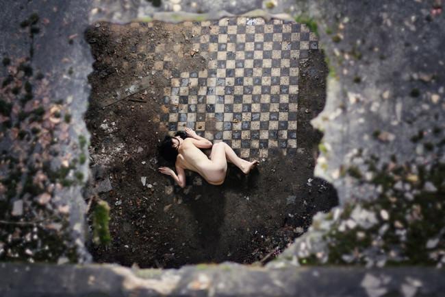 Eine Frau liegt auf einem Fliesenboden mit Perspektive von oben.
