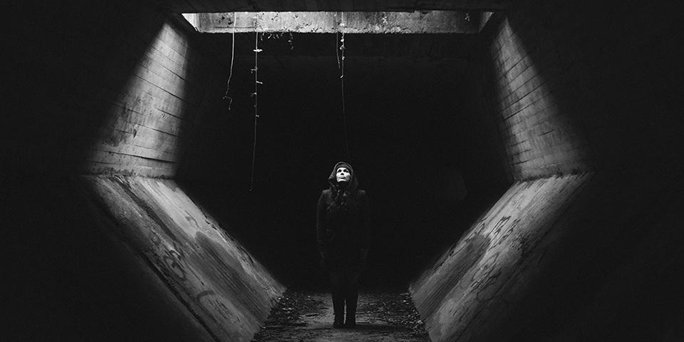 Eine Frau in einem Tunnel unter einem Lichtschacht.