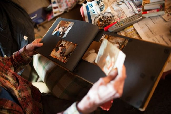 Alte Hände halten ein Fotoalbum.