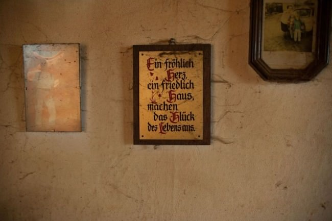Wand mit zwei gerahmten Bildern und einem Hausspruch.