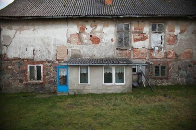 Ein großes, verfallenes Haus auf einem ländlichen Grundstück.