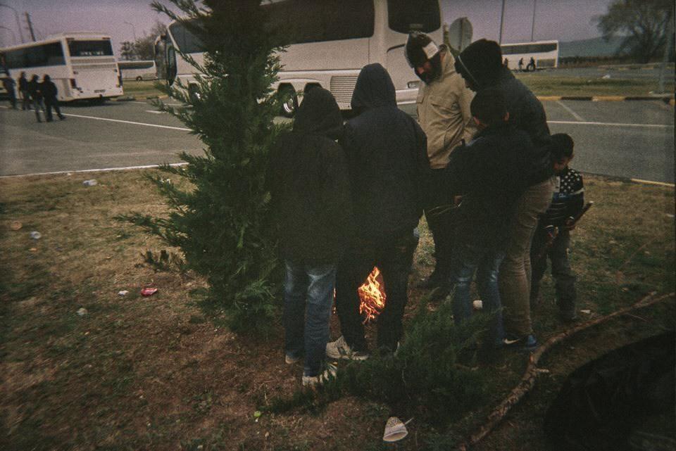 Menschen stehen um ein Feuer am Busbahnhof