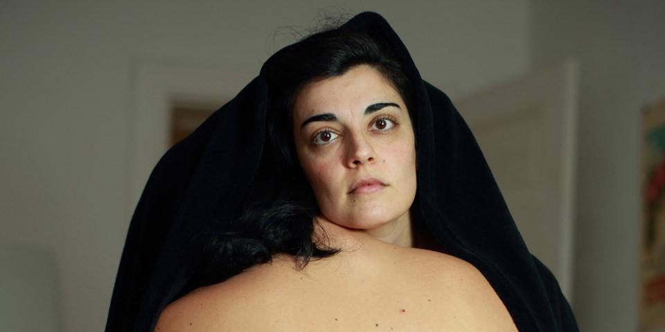 Eine Frau schaut unter einem schwarzen Tuch hevor.