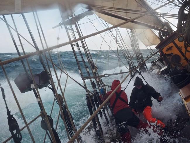 Eine große Welle bricht über ein Schiff herein