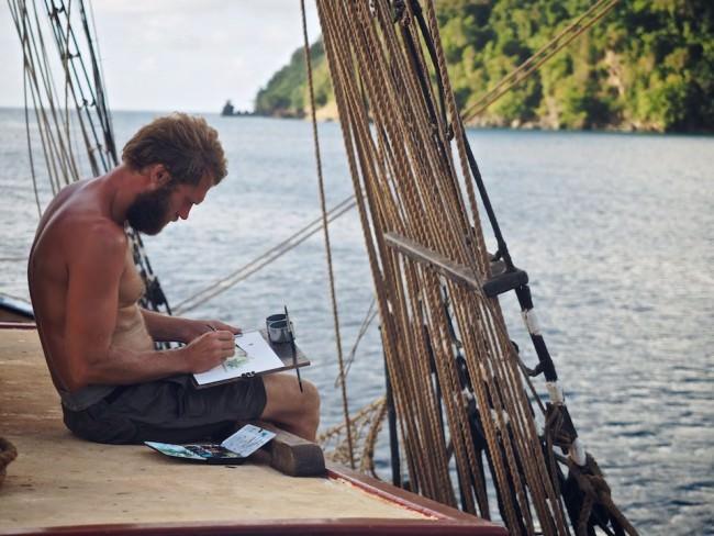 Ein Mann malt auf Deck ein Bild