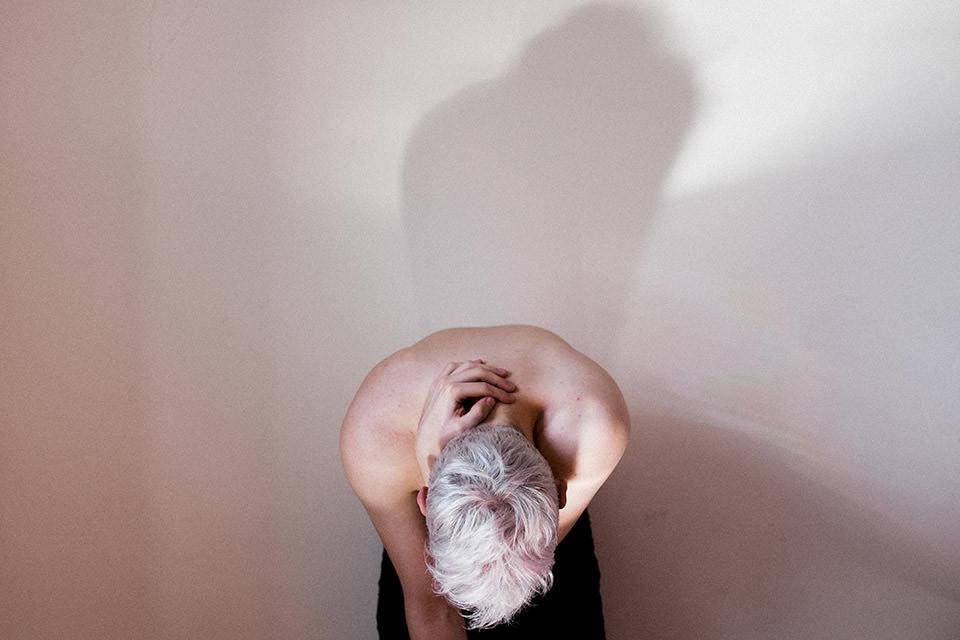 Ein Mann verbeugt sich, sein Schatten nicht.