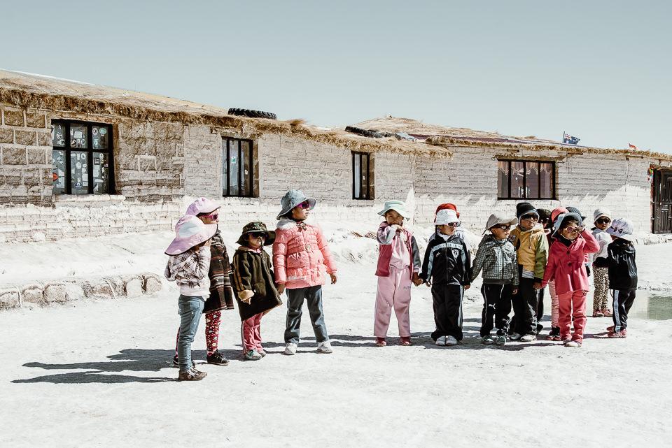 Kinder stehen vor einigen Hütten