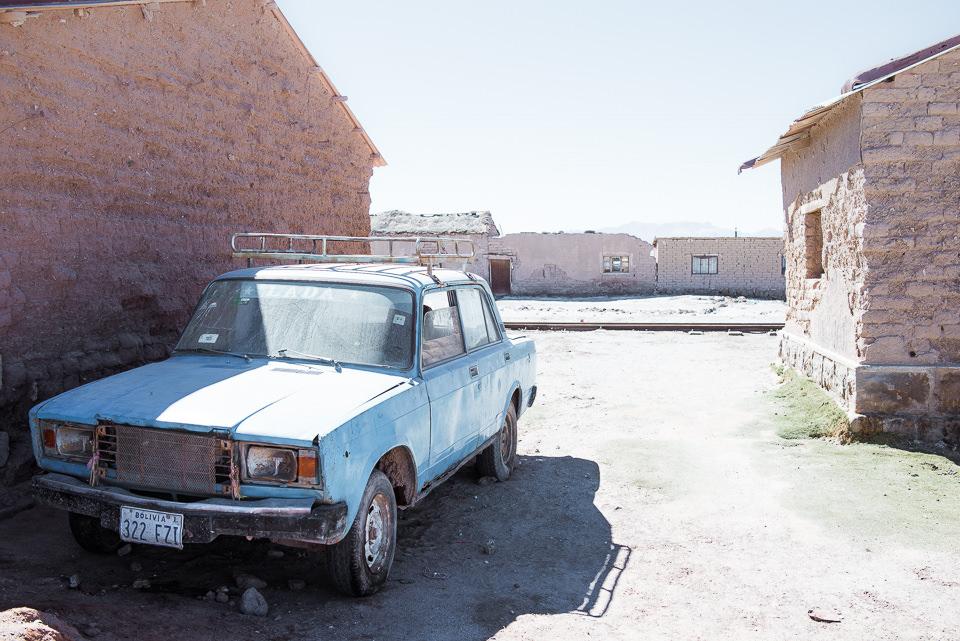 Ein blaues Auto neben einer Hauswand