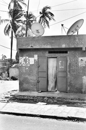 Ein Betonhaus mit Satelittenschüsseln auf dem Dach und offener Tür.