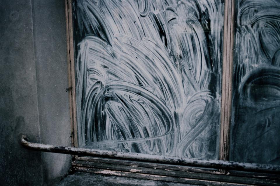 Verschmierte Seifenreste auf einer Fensterscheibe.