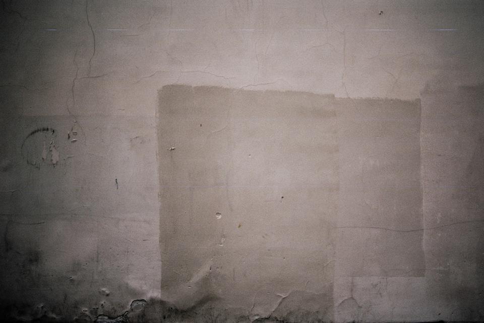 Eine weiße Wand mit Tapetenresten.