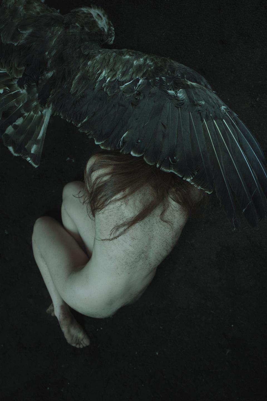 Der Flügel eines großen Vogels ist über dem Kopf einer nackten Frau.