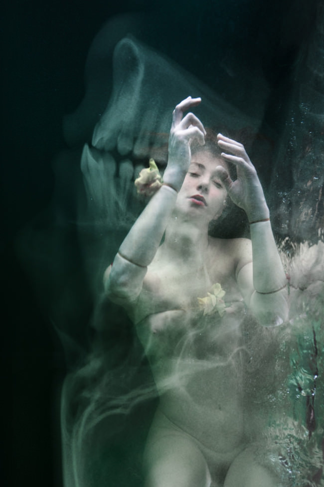 Eine Frau, die wie eine Puppe verkleidet ist, teucht steif im Wasser.