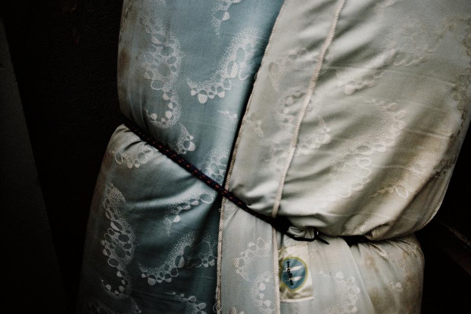 Eine Matratze mit Samtüberzug ist zugeschnürt.