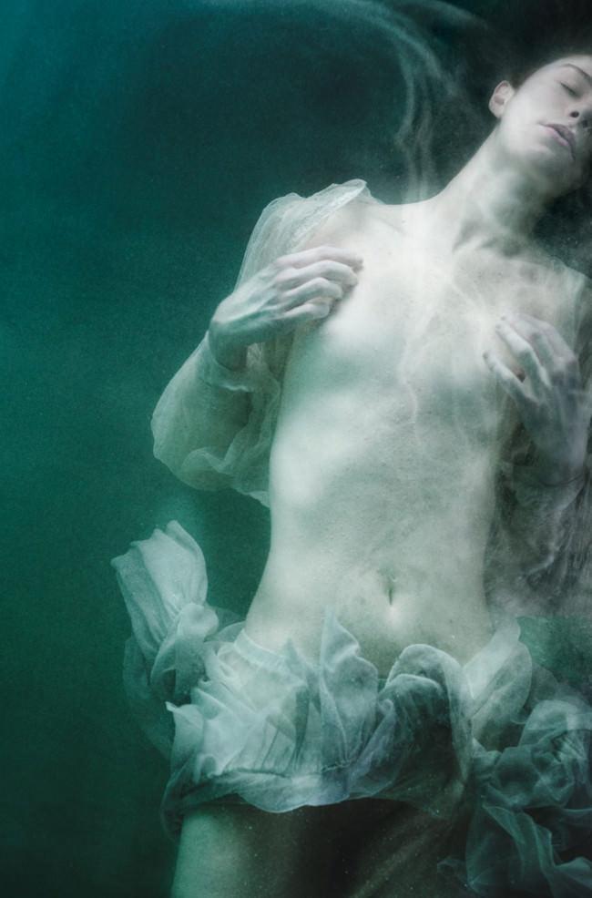 Eine Frau in wehendem Tüll taucht.
