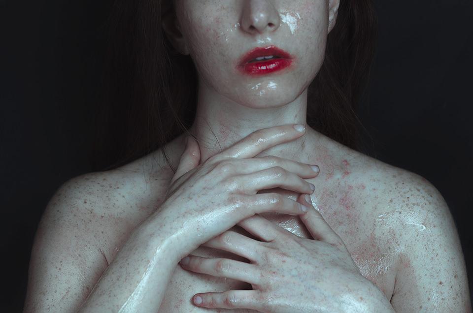 Eine nasse, nackte Frau trägt verschmierten Lippenstift.